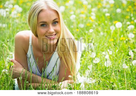 Beautiful young woman in a clearing among the flowers