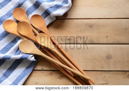 Wooden mixing spoons and dish towels on an old kitchen table top.