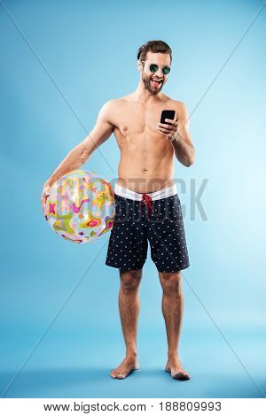 Full length portrait of a handsome young guy holding beach ball and typing message on mobile phone isolated over blue