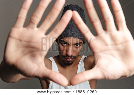 Picture of young african man isolated over grey background. Looking at camera showing hands to camera.