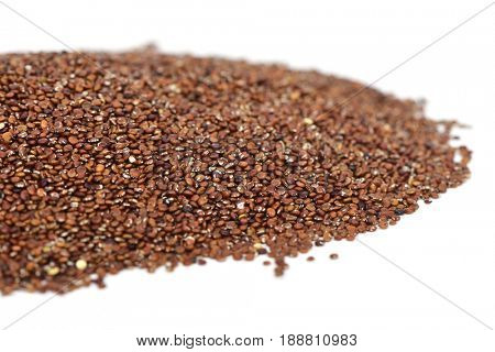 closeup of a pile of red quinoa seeds on a white background