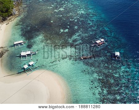 Aerial view of tropical island beach with boats and turquoise sea. Palawan May 2017