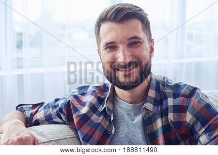 Close-up of smiling bearded mister leaning on back oh sofa and having rest