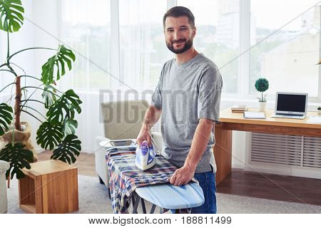 Mid shot of sportive guy ironing diligently shirt on ironing board