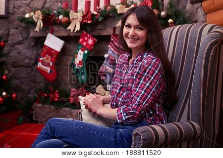 Close-up of Joyous girl sitting in an armchair with a background of decorated fireplace with Christmas stockings. The concept of Christmas and holidays. New Year celebration