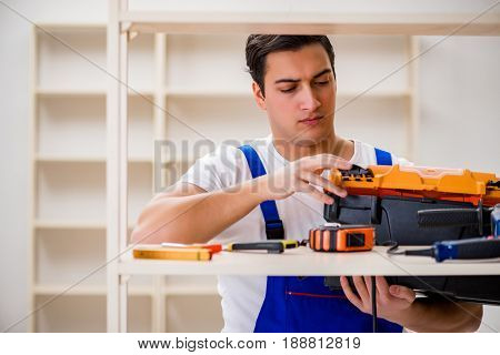 Worker man repairing assembling bookshelf