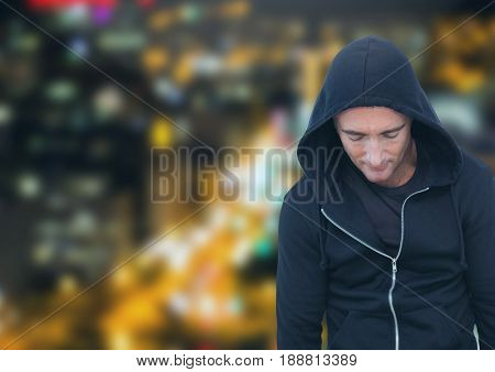 Digital composite of Criminal in hood in front of night city