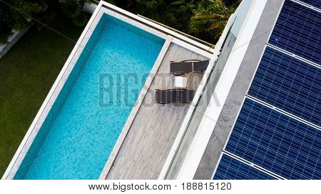 Top view of outdoor swimming pool and solar panels on the roof of villa