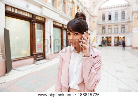 Upset young girl receiving bad news while talking on mobile phone at the city street