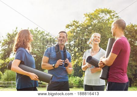 Group of multiethnic people talking to each other after exercising at park. Couples in a conversation after enjoying yoga session outdoor. Cheerful group of mature friends relaxing after yoga.