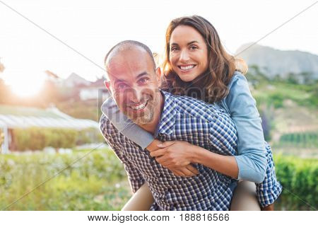 Happy mature couple enjoying outdoors during sunset. Smiling woman piggyback on her man while looking at camera. Portrait of middle aged man carrying on shoulder his wife.