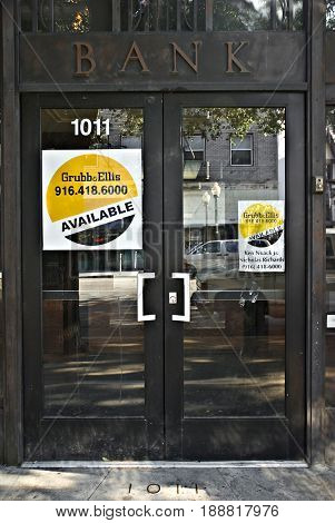 SACRAMENTO, CALIFORNIA, USA - November 14, 2009: Grubb and Ellis for sale signs in a bank doorway'??s windows