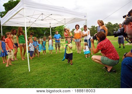 SACRAMENTO, CALIFORNIA, USA - July 11, 2009: Group of amateur photographers shooting pictures of a large group of children and their moms
