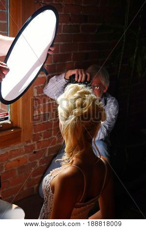 SACRAMENTO, CALIFORNIA, USA - September 18, 2009: Blonde model poses for a photographer with an assistant lights her face with a reflector during Sacramento Fashion Week