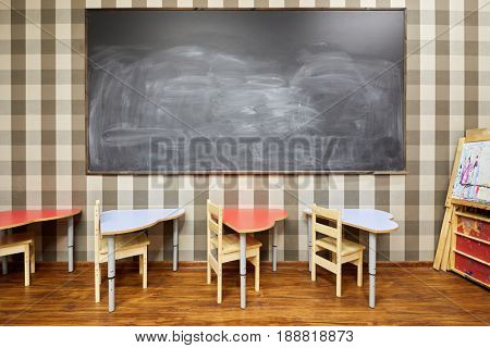 Blackboard on wall and desks with chairs in classroom at chidren club.
