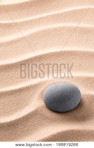 Round stone laying on rippled beach sand. Zen meditation minimalism. Concept for relaxation and concentration.