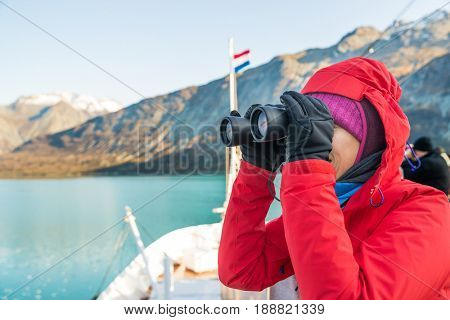 Tourist looking at Alaska Glacier Bay landscape using binoculars on cruise ship. Woman on vacation travel looking for wildlife enjoying cruising famous tourist destination.