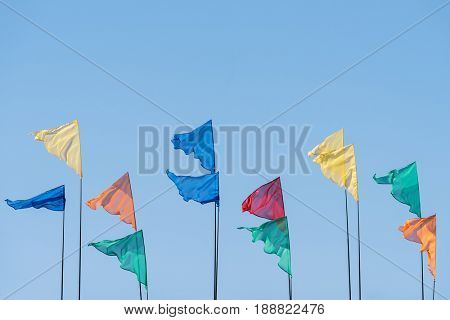 Flags of different colors against the blue sky. Festive background