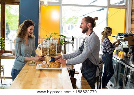 Waiter serving a cup of coffee to customer at counter in cafe