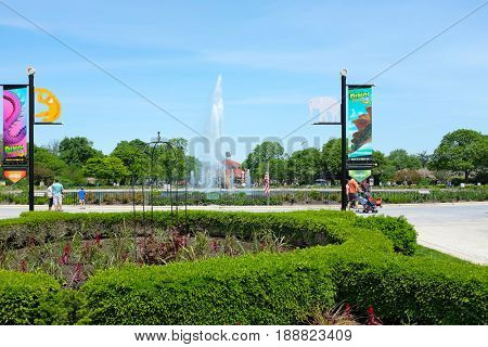 BROOKFIELD, ILLINOIS - MAY 27, 2017: Roosevelt Fountain at the Brookfield Zoo. The foreground shows banners for the Dinos Exhibit and in the background is the popular Carousel Ride.