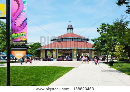 BROOKFIELD, ILLINOIS - MAY 27, 2017: The Carousel at Brookfield Zoo. The ride is popular attraction of the park with families and children. A banner announcing the Dinos Exhibit is in the foreground.