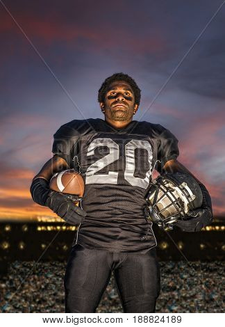 African American football player holding helmet and ball
