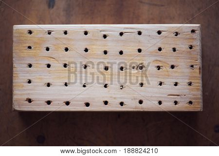 Full of holes. a piece of 2 x 4 lumber with many holes drilled in it.