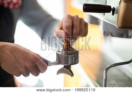 Waiter using a tamper to press ground coffee into a portafilter in cafe
