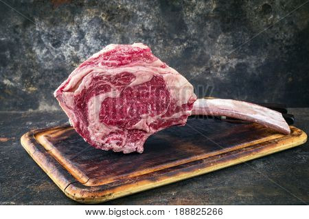 Raw dry aged Wagyu Tomahawk Steak as close-up on old cutting board