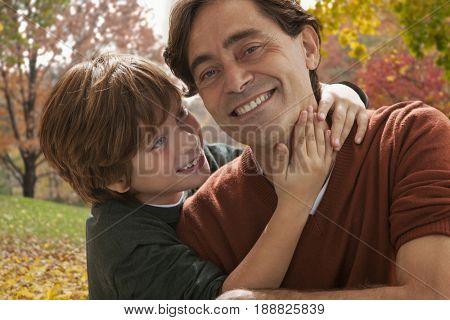 Caucasian boy hugging father