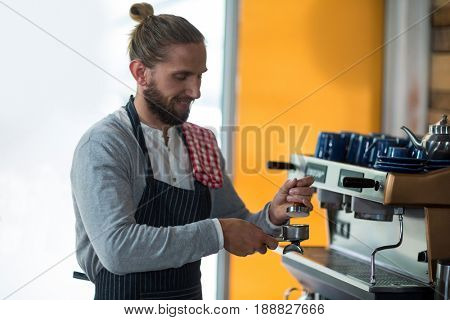 Waiter using a tamper to press ground coffee into a portafilter in café