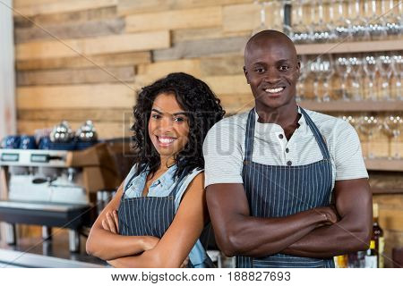 Portrait of smiling waiter and waitress standing back to back at counter in cafe