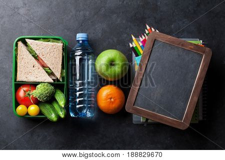 Lunch box with vegetables and sandwich. Kids take away food box and school supplies. Top view on blackboard with space for your text