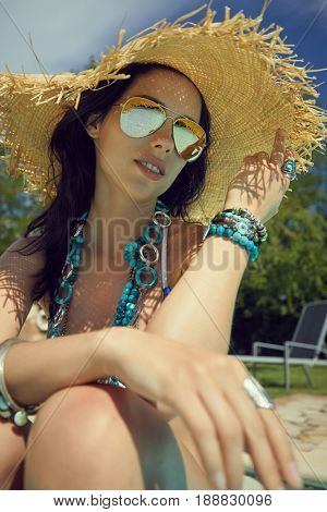 Beautiful woman in sun hat sunbathing on air mattress in the swimming pool