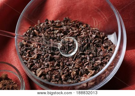 Bowl with cocoa nibs on color cloth background