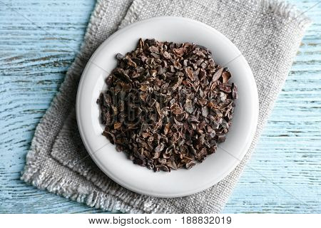 Plate with cocoa nibs on wooden table
