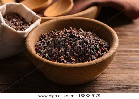 Bowl with cocoa nibs on wooden table