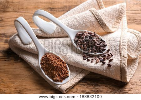 Two spoons with cocoa nibs and powder on wooden table