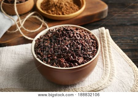 Bowl with cocoa nibs on table
