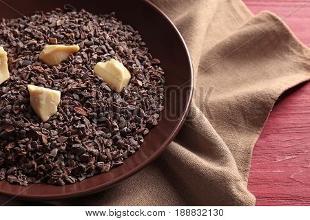 Bowl with cocoa nibs and butter on table