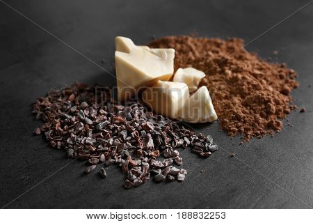 Cocoa nibs, butter and powder on gray background