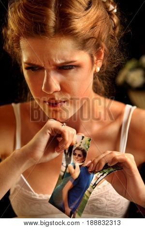Sad bride on unhappy wedding. Woman and groom quarrel. Girl in white dress tearing love pictures. Portrait crying female. Candle and wedding ring are on table.