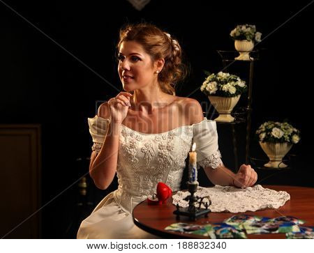 Bride thinking about choice of groom. Woman in wedding dress dreams of holiday night. Girl is preparing for ceremony. Candle stands on table decorated with lacy napkin on black background.