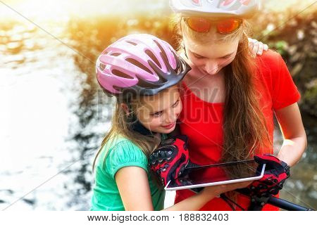 Bikes cycling girl. Children rides bicycle. Bicyclist girl watch on tablet computer. Kids looking for way. Dependence of adolescents on gadgets. Sports orienteering.