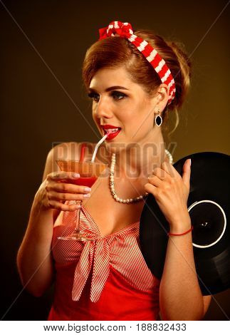 Retro woman with music vinyl record. Pin up girl drink martini cocktail . Girl pin-up retro style wearing red dress on dark background.