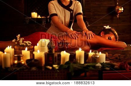 Massage of woman in spa salon. Girl on candles background treats problem back . Luxary interior with working masseuse . Shirodhara Pot background. Crop of bare back has relax . Alternative medicine.