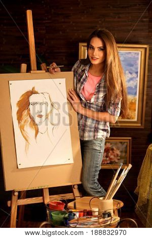 Artist painting on easel in studio. Girl paints portrait of woman with brush. Female draws self-portrait. Indoor home interior for handmade crafts. Fashionable style of drawing.