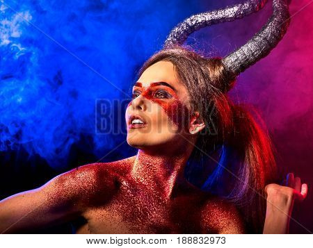 Mad satan woman on black magic ritual of in hell . Witch reincarnation mythical creature on Sabbath. Devil absorbing soul Halloween. Zodiac Capricorn Aries , Taurus astrology. Make-up for night club.