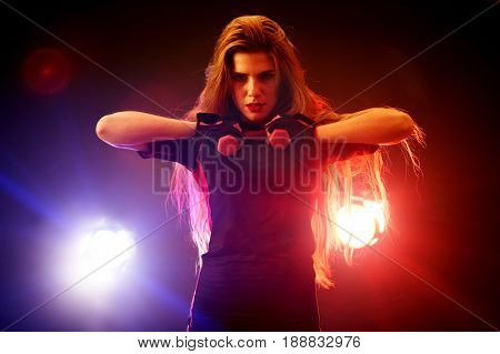 Boxing women fitness exercises in gym. Sport workout on ring .Boxer wearing red gloves to box in ring. Martial arts female in neon rays of light.