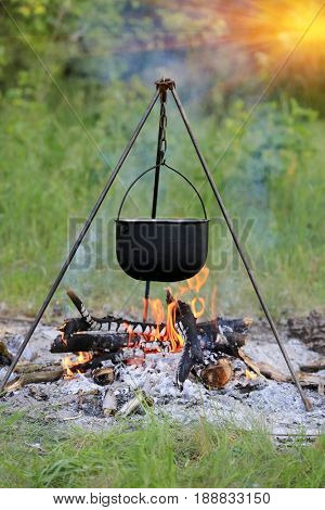 Smoked tourist kettle over fire in forest camp